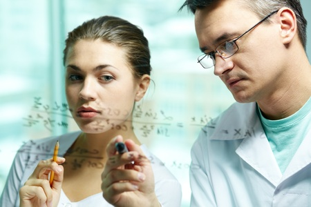 compound: Serious scientist explaining chemical formula to his co-worker