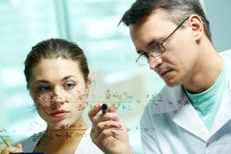 Serious scientist explaining chemical formula to his co-worker  photo