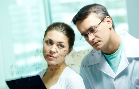 trigonometry: Serious chemists looking at formula on transparent board