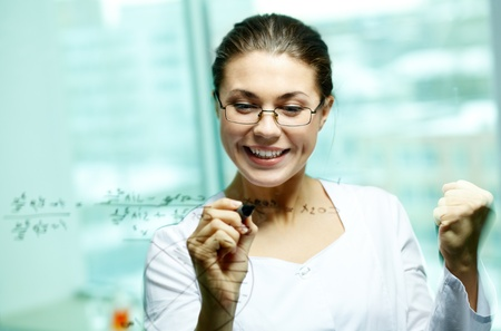Happy young woman looking at board while writing on it photo