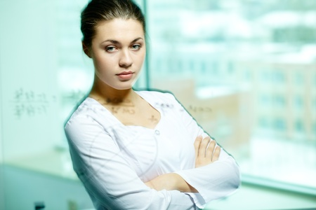 Serious chemist looking at transparent board with pensive expression Stock Photo - 11448630