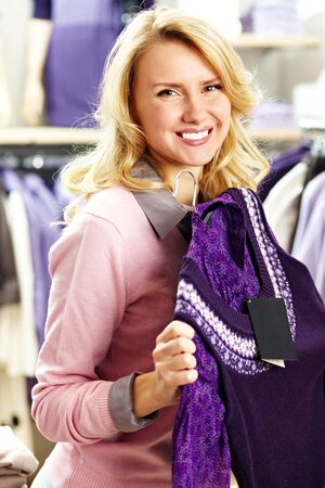 Portrait of pretty woman with violet cardigan looking at camera in clothing department Stock Photo - 11448746