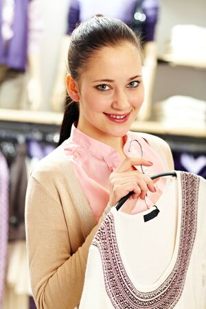 Portrait of pretty woman holding cardigan and looking at camera in clothing department photo