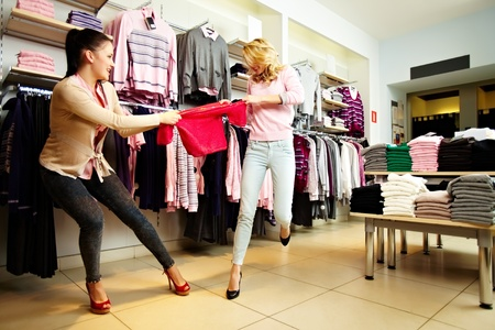 reluctant: Image of two greedy girls fighting for red tanktop in department store Stock Photo