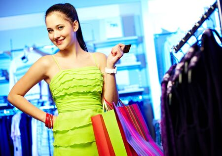 Portrait of pretty woman with paperbags and plastic card looking at camera in clothing department photo