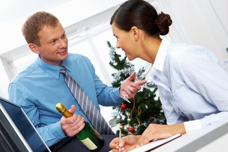 Portrait of young businessman with bottle of champagne and two flutes offering his colleague to drink for New Year Stock Photo - 11448697