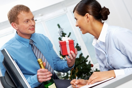 Portrait of young businessman with bottle of champagne giving present to his colleague photo