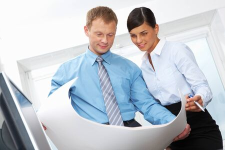 Two office workers looking at blueprint at meeting Stock Photo - 11448688