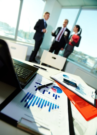 meeting place: Image of business documents on workplace with three partners on background Stock Photo