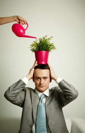 Photo of serious man with plant on head being watered from watering pot photo