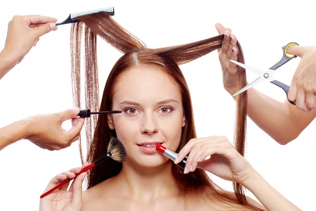 beauty salon face: Portrait of young female surrounded by hands with beauty tools looking at camera