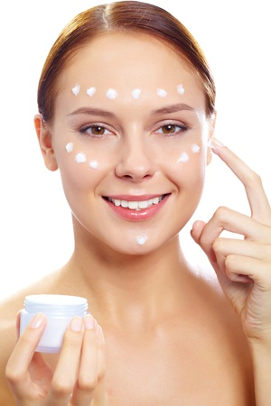 Fresh woman holding container with facial cream and applying it onto her face photo