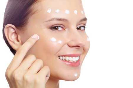 Fresh woman applying hydrating cream onto her face photo