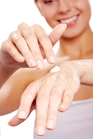 handcare: Image of female hands being treated with handcream on white background