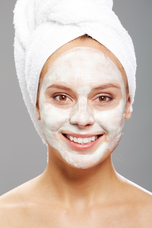 purifying: Fresh woman with facial mask looking at camera with smile Stock Photo