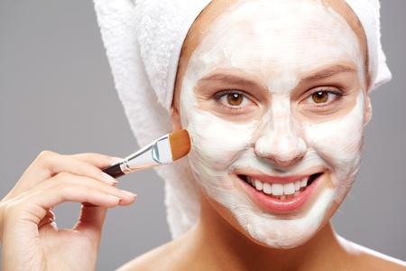 Femme fraîche application d'un masque facial sur le visage avec une brosse Banque d'images
