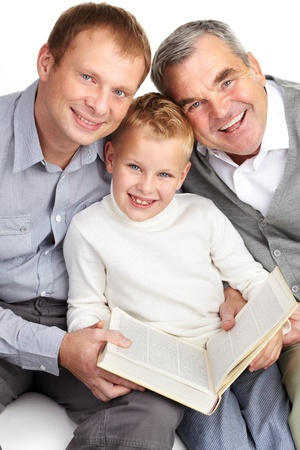 Portrait of father, grandfather and son looking at camera while reading a book photo