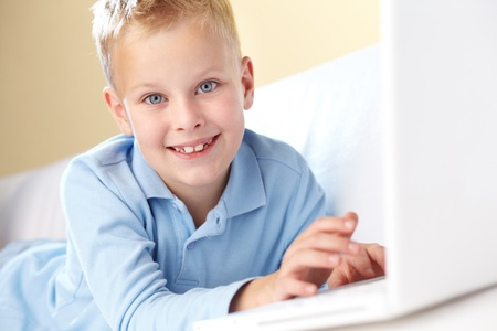 Portrait of cute boy typing and looking at camera photo