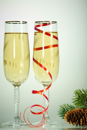 Two champagne flutes with firtree cone on conifer branch near by photo
