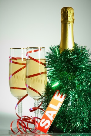 Two champagne flutes with green tinsel, bottle of champagne and sale tag near by photo