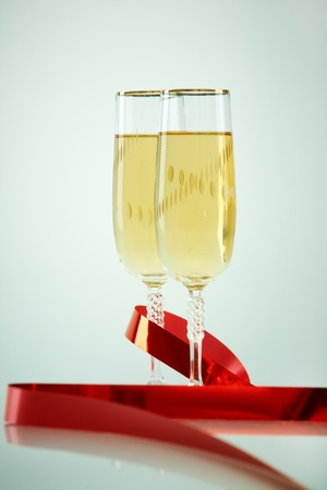 Two champagne flutes with red ribbon near by photo