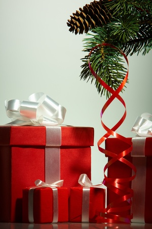 natale: A heap of Christmas giftboxes with red ribbon and coniferous branch near by Stock Photo