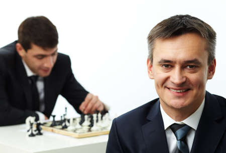 Image of happy businessman looking at camera while his colleague on background playing chess photo