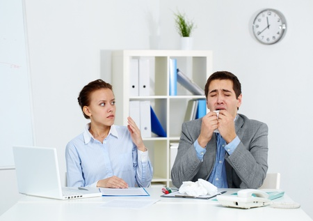 Image of businessman sneezing while his partner looking at him with anxiety in office  photo