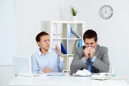 infect: Image of sick businessman sneezing while anxious female looking at him in office  Stock Photo