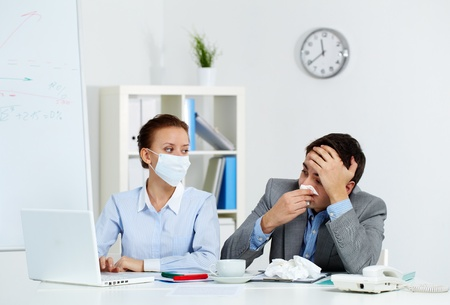 Image of sick businessman with tissue looking at laptop screen with his colleague wearing mask neaer by in office  photo