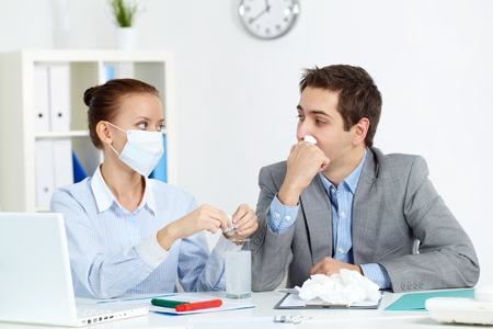 Image of sick businessman with tissue looking at his colleague in mask dissolving solution for him in office photo