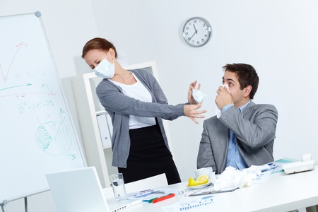 Image of businessman with handkerchief by nose and his disgusted partner in mask offering him to put on one in office  photo