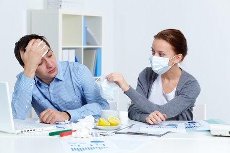 Image of sick businessman looking at his partner in mask offering him to put on one in office  photo