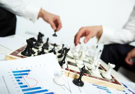 �checs: Image de deux �v�ques sur les papiers d'affaires avec les mains de l'homme jouant aux �checs sur fond