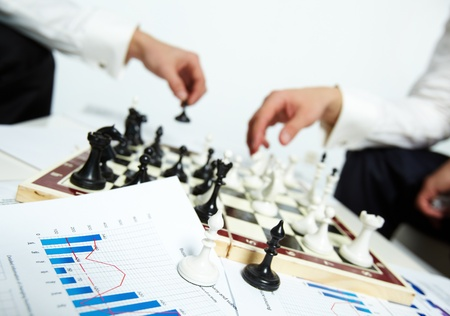 Image of two bishops on business papers with human hands playing chess on background