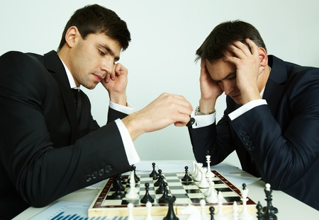 rival: Image of businessman making move while playing chess with his rival in front of him