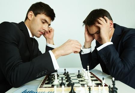 jugando ajedrez: Imagen de hombre de negocios haciendo pasar mientras jugaba al ajedrez con su rival delante de él