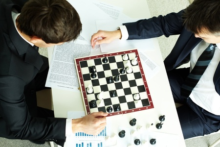 Image of two businessmen looking at chessboard while playing chess photo