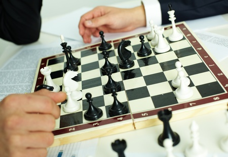 Image of chess figures on chessboard with human hands near by photo
