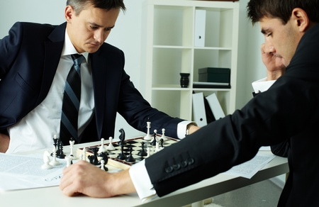 playing chess: Image of two businessmen looking at chessboard while playing chess