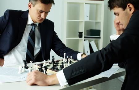 jugando ajedrez: Imagen de dos hombres de negocios mirando tablero de ajedrez, mientras que jugar al ajedrez Foto de archivo