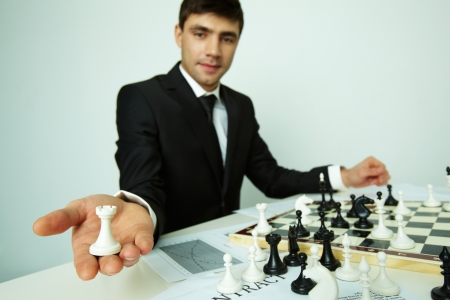 chess player: Image of successful businessman looking at camera while showing rook figure