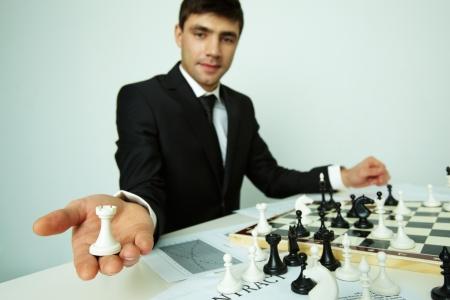 jugando ajedrez: Imagen de exitoso hombre de negocios mirando a la cámara mientras se muestra la figura torre Foto de archivo