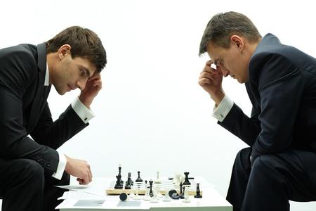 jugando ajedrez: Imagen de dos hombres de negocios pensando en moverse mientras juegan al ajedrez
