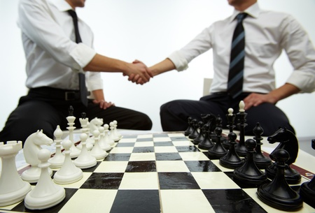 Four rows of chess figures on chess board with two men handshaking on background photo