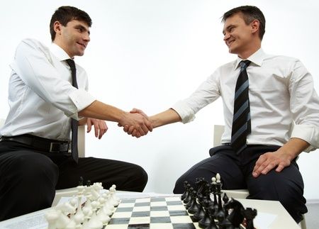 Two men handshaking with chess figures on chess board near by photo