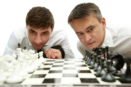 Two men looking at chess figures on chess board photo