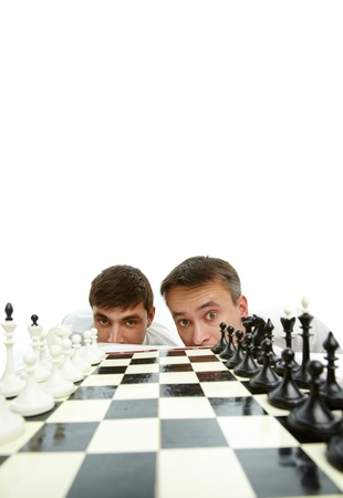 Two men looking at camera with chess board in front photo
