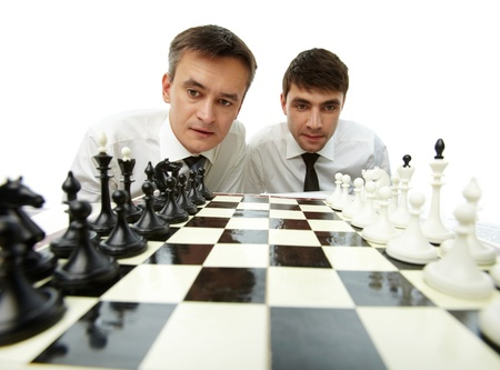 chess knight: Two men looking at chess figures on chess board Stock Photo