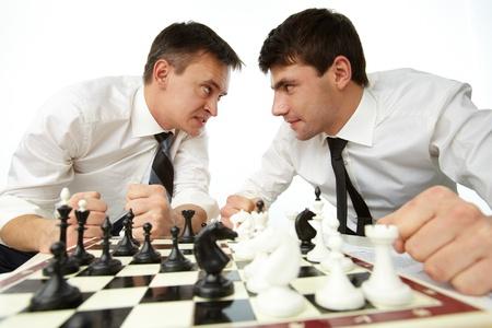 aggressively: Due uomini che cercano l'un l'altro in modo aggressivo, mentre giocano a scacchi